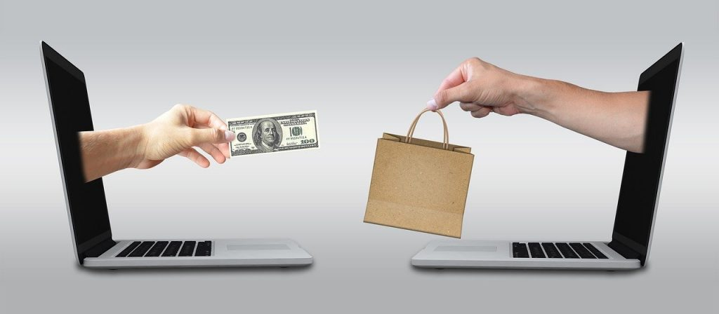 image of two laptop computers faceing each otehr with arms coming out of the screen, arm on the left has a one hundred dollar bill and is a female hand and the arm on the right is a male hand with a small brown bag with string type handles. Indicative of online selling and online buying of items.