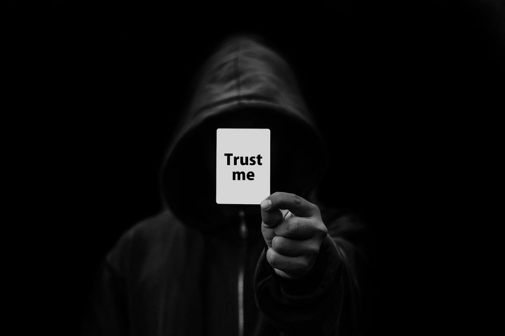 Image of a dark background with a man in a black hoodie holding a trust me card up indicated of shady charachters selling online.
